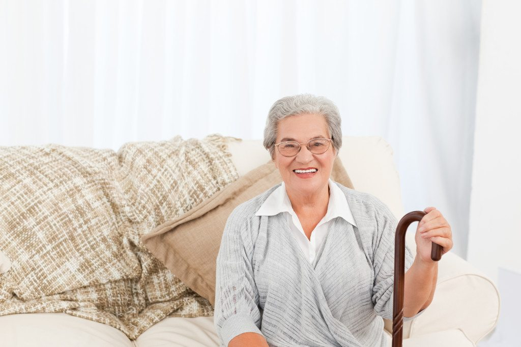 Mature woman sitting on the sofa with her walking stick at home