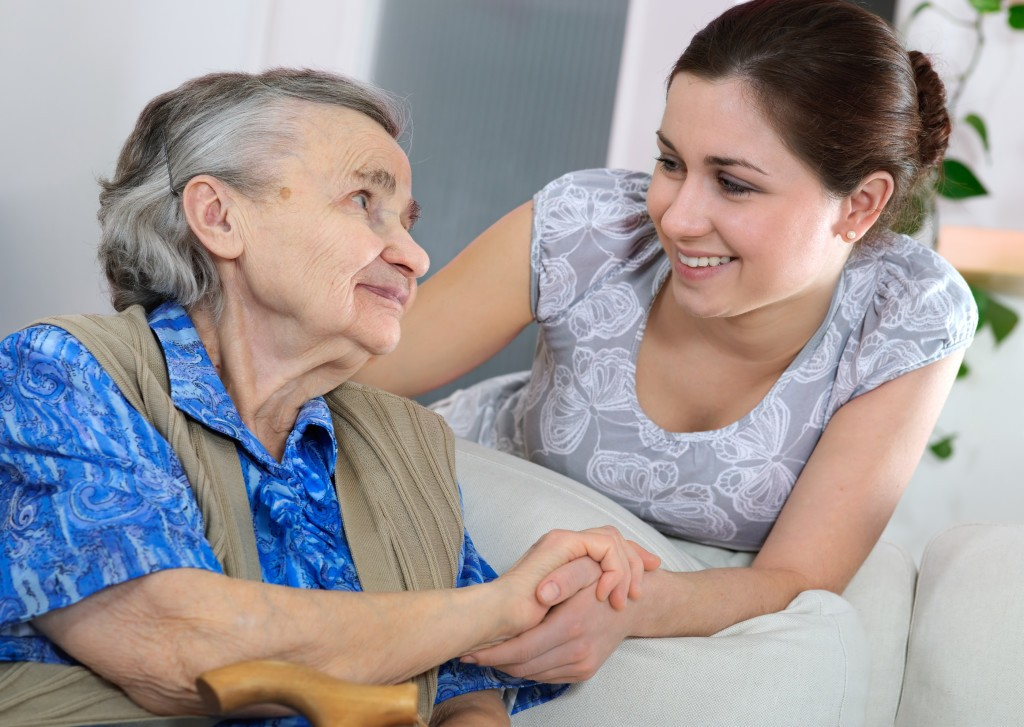 Senior woman with her home young caregiver